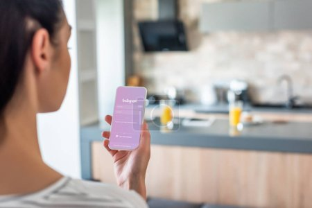 selective focus of woman holding smartphone with instagram logo on screen in kitchen