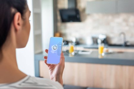 selective focus of woman holding smartphone with shazam logo on screen in kitchen