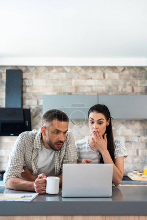 portrait of shocked married couple looking at laptop screen together at counter in kitchen