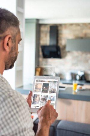 Photo pour Foyer sélectif de l'homme utilisant la tablette numérique avec le site Web de pinterest à l'écran dans la cuisine - image libre de droit