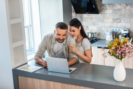 portrait of married couple using laptop together at counter in kitchen