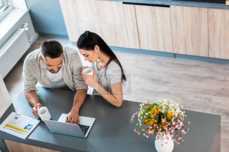 high angle view of married couple with cups of coffee using laptop together at counter in kitchen