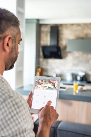 selective focus of man using digital tablet with foursquare website on screen in kitchen