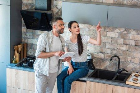 pareja casada con tableta digital mirando hacia otro lado en la cocina, concepto de hogar inteligente