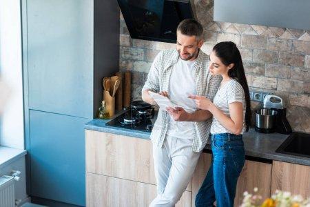 Photo pour Couple marié à l'aide de la tablette numérique ensemble dans la cuisine, le concept de maison intelligente - image libre de droit