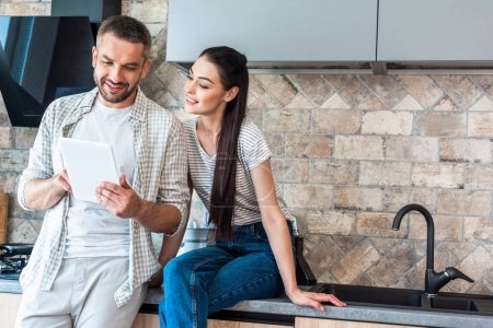 portrait of smiling couple using digital tablet together in kitchen, smart home concept