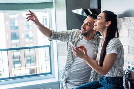 Photo pour Vue latérale du sourire couple avec smartphone vous cherchez loin ensemble dans la cuisine, le concept de maison intelligente - image libre de droit