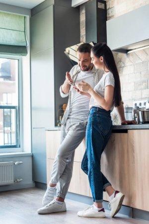 pareja usando el teléfono inteligente juntos en la cocina, concepto de hogar inteligente