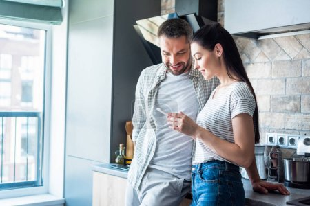 smiling couple using smartphone together in kitchen, smart home concept