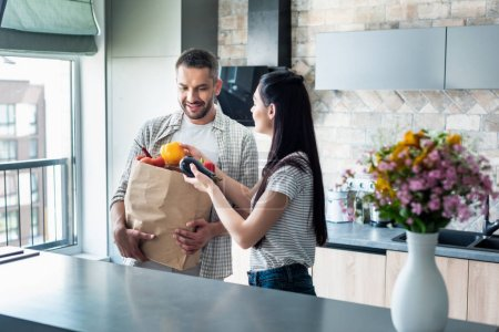 married couple with paper package full of fresh vegetables for dinner in kitchen at home