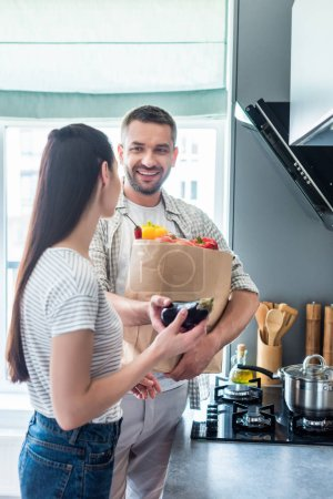 happy married couple with paper package full of fresh vegetables for dinner in kitchen at home