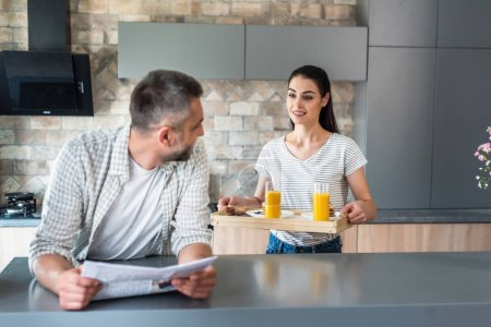 man with newspaper standing at counter and looking at wife with breakfast on wooden tray in kitchen