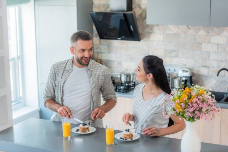 portrait of married couple having breakfast together in kitchen