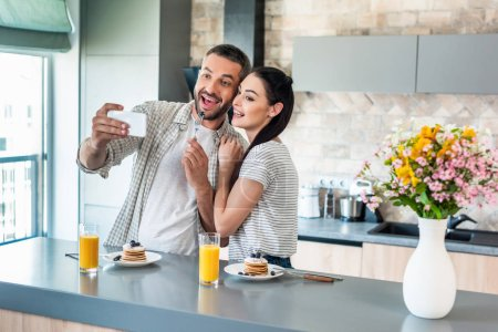 smiling couple taking selfie on smartphone at counter with homemade breakfast in kitchen