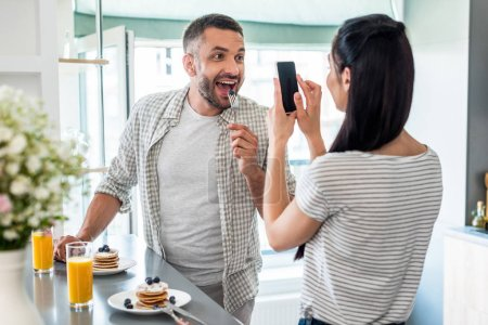 woman taking picture of husband playing with breakfast at counter in kitchen