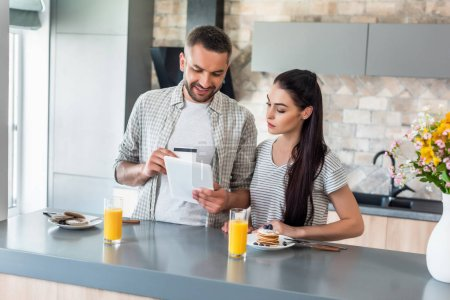 portrait of couple using tablet at counter with homemade breakfast in kitchen
