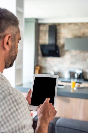 selective focus of man using tablet with blank screen in kitchen
