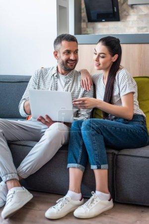 Photo pour Couple utilisant un ordinateur portable ensemble tout en se reposant sur le canapé à la maison - image libre de droit