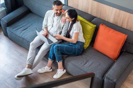 Photo pour Vue grand angle du couple en utilisant un ordinateur portable ensemble tout en se reposant sur le canapé à la maison - image libre de droit