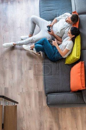 Photo pour Vue aérienne du couple marié avec des manettes de jeu jouant ensemble à des jeux vidéo assis sur le canapé à la maison - image libre de droit