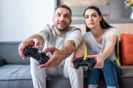 selective focus of married couple with gamepads playing video games together while sitting on sofa at home