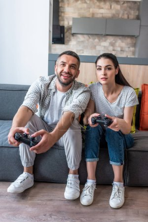 married couple with gamepads playing video games together while sitting on sofa at home