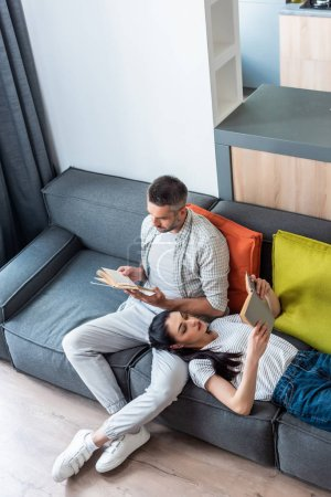 high angle view of couple reading books on couch at home