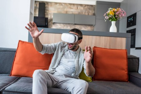emotional man wearing virtual reality headset while sitting on sofa at home