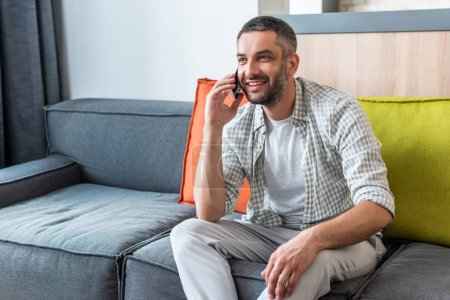 smiling bearded man sitting on sofa and talking on smartphone at home