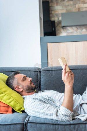 Photo pour Vue latérale du livre de lecture d'homme barbu en position couchée sur le canapé à la maison - image libre de droit