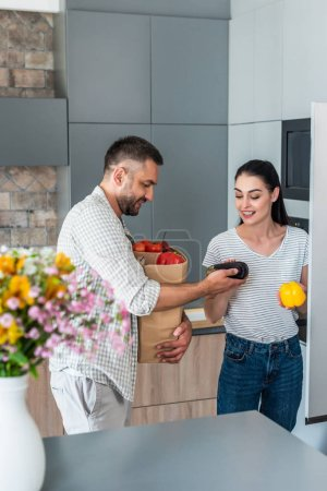 smiling married couple putting fresh vegetables into fridge in kitchen at home