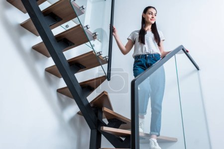 Photo for Low angle view of smiling woman in jeans looking away while standing on stairs at home - Royalty Free Image
