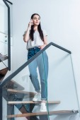 low angle view of attractive woman talking on smartphone while standing on stairs at home