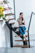 woman with cup of coffee in hand talking on smartphone while sitting on stairs at home