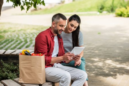 side view of married couple using tablet together while resting after shopping on bench on street