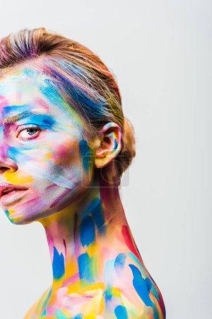 image recadrée de fille attrayante avec un art du corps lumineux coloré en regardant la caméra isolée sur blanc