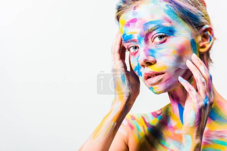 attractive girl with colorful bright body art touching face and looking at camera isolated on white