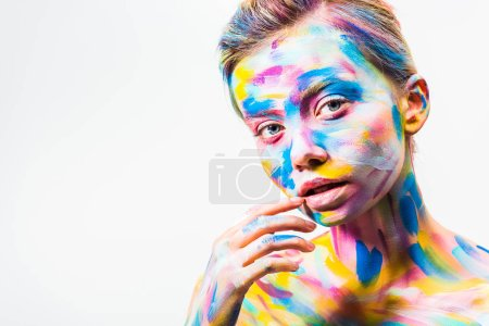 attractive girl with colorful bright body art touching lip isolated on white