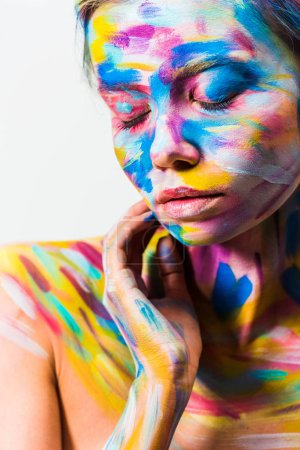 attractive girl with colorful bright body art with closed eyes isolated on white