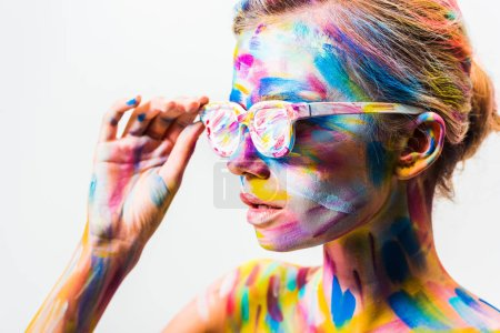 attractive girl with colorful bright body art touching sunglasses isolated on white