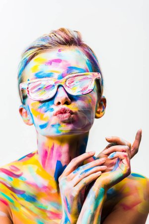 attractive girl with colorful bright body art and sunglasses sending air kiss isolated on white