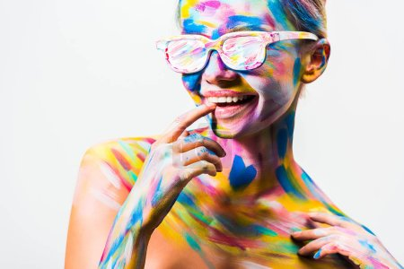 smiling attractive girl with colorful bright body art and sunglasses touching lips isolated on white