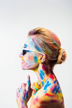 Photo for Side view of smiling attractive girl with colorful bright body art and sunglasses isolated on white - Royalty Free Image