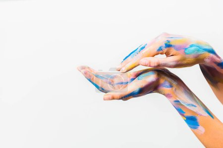 cropped image of girl with colorful bright body art making waves with hands isolated on white