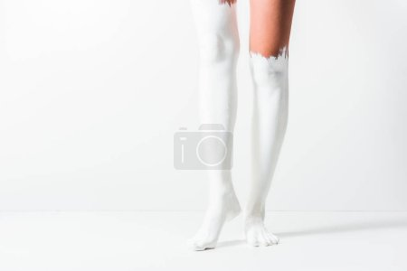 cropped image of girl with legs painted with white paint standing on white