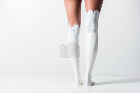 cropped image of girl with legs painted with white paint standing on white floor