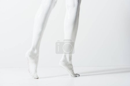 cropped image of girl with legs painted with white paint walking on white floor