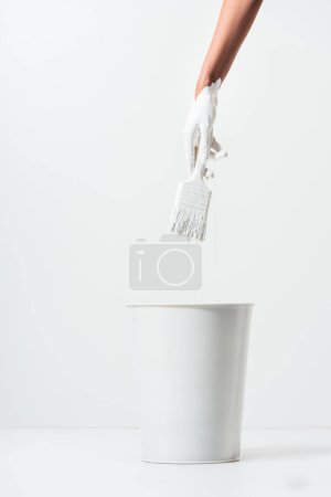 cropped image of woman holding painting brush with white paint above bucket on white