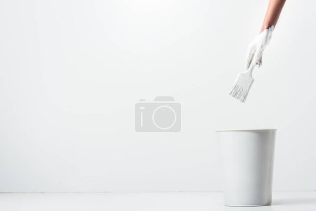 cropped image of girl holding painting brush with white paint above bucket