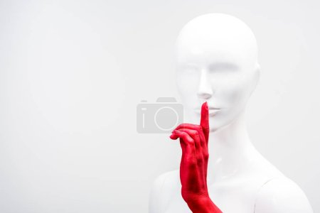 Photo for Cropped image of woman in red paint showing silence gesture with mannequin isolated on white - Royalty Free Image